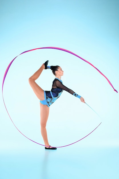 A garota fazendo ginástica dança com fita colorida em uma parede azul Foto gratuita