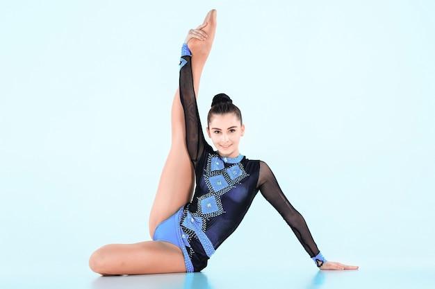 A garota fazendo ginástica dançar em uma parede azul Foto gratuita
