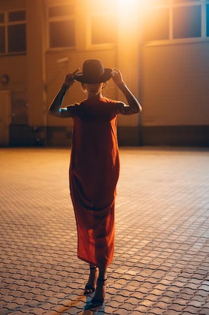 A garota jovem e atraente com um chapéu posa para a câmera à noite Foto gratuita