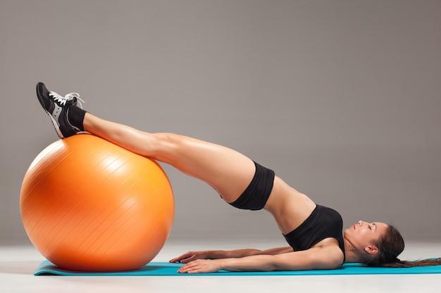 A garota jovem e bonita de esportes fazendo exercícios em uma fitball Foto gratuita