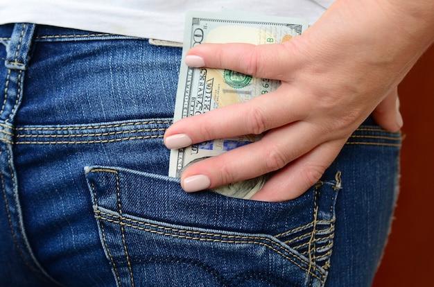 A garota leva um monte de notas de dólar do bolso de trás das calças de brim Foto Premium