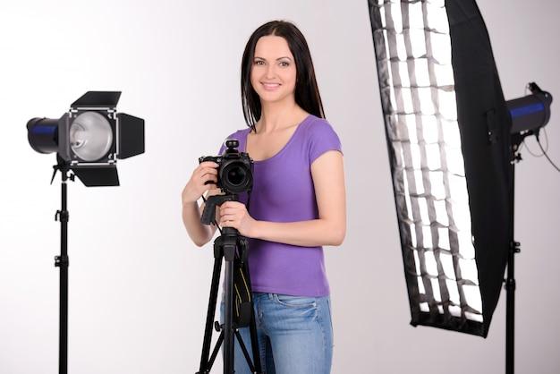 A garota no estúdio de fotografia trabalha e sorri. Foto Premium