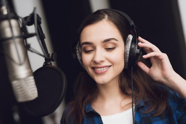 A garota no estúdio de gravação canta uma canção Foto Premium