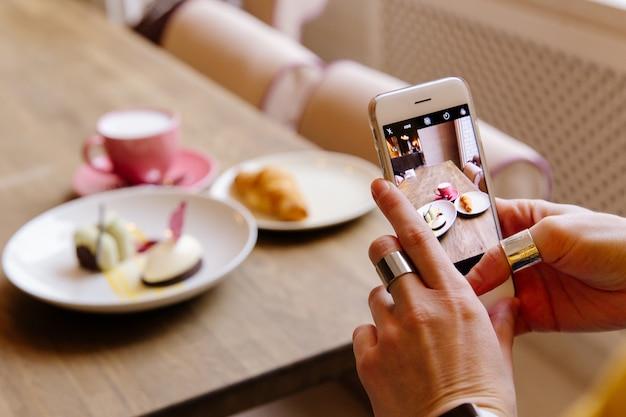 A garota no restaurante fotografando a comida no telefone. Foto Premium