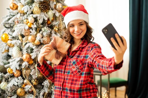 A garota posa e tira uma selfie perto da árvore de natal. uma mulher parabeniza um parente online por telefone. ela está segurando um presente na mão e sorrindo. Foto Premium