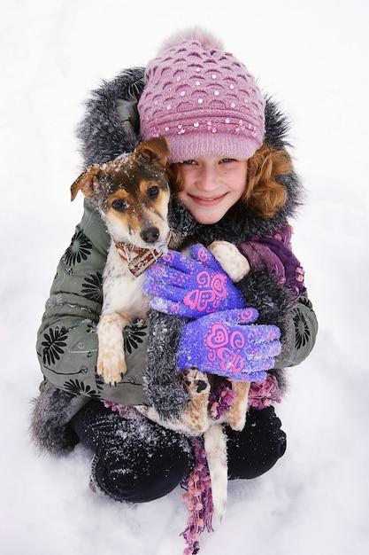 A garota se senta na neve e segura nas mãos de seu amado cachorro. infância feliz. amor aos animais Foto Premium