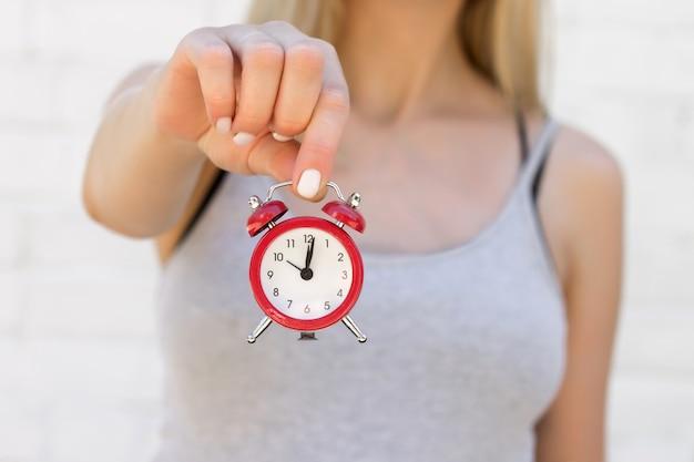 A garota tem um despertador vermelho na mão estendida. tempo, sono, conceito de despertar Foto Premium