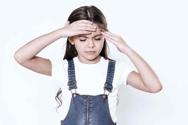 A garota tem uma dor de cabeça. ele segura a mão dela na cabeça dela. Foto Premium