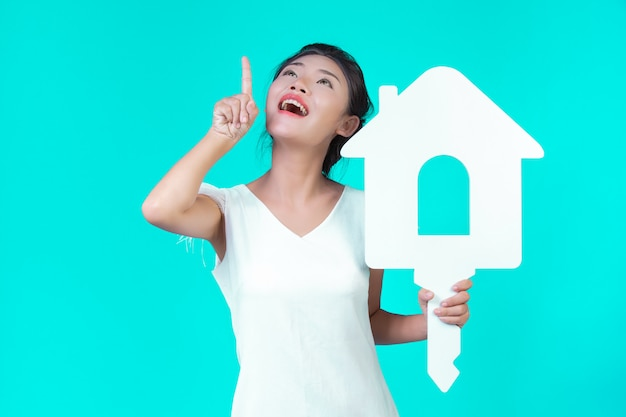 A garota usava uma camisa branca de mangas compridas com padrão floral, segurando o símbolo da casa e mostrando vários gestos com um azul. Foto gratuita