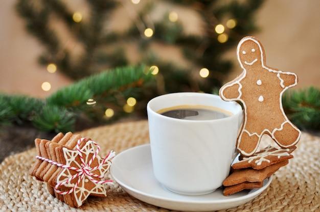 A geada tradicional do açúcar do pão-de-espécie do natal deu forma como um homem pequeno engraçado e um copo do café quente em de madeira. Foto Premium