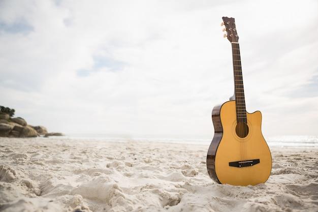 A guitarra que está acústico na areia Foto gratuita