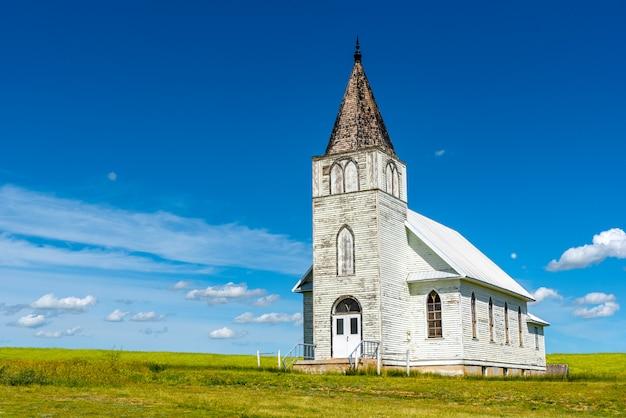 A histórica igreja luterana de immanuel no almirante, saskatchewan, com um campo de canola Foto Premium