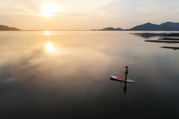 A ideia aérea da silhueta de levanta-se o pensionista da pá que rema no por do sol em um rio quieto morno liso. Foto Premium