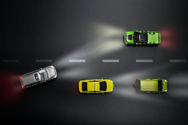 A ideia superior do carro brinca o modelo na estrada na noite com conceito de condução descuidado. Foto Premium