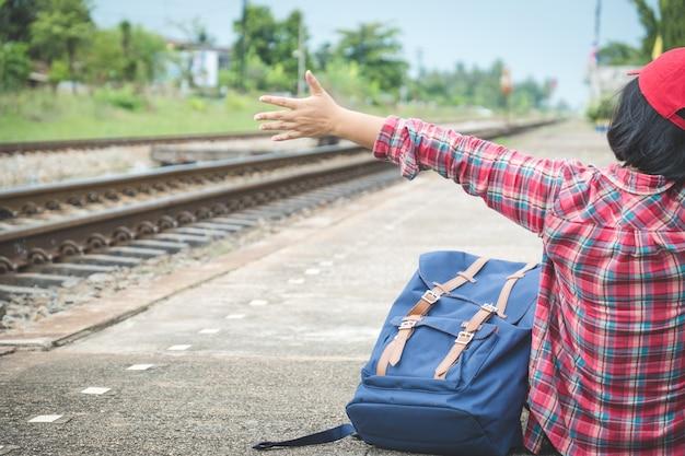 A ideia traseira do assento do turismo da jovem mulher (passageiro) e mostra sua mão na plataforma no estação de caminhos-de-ferro. à espera de transporte Foto Premium