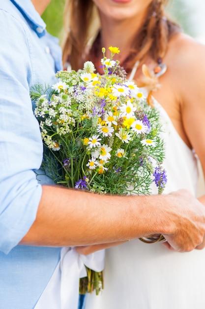 A imagem da colheita do casal romântico com flores Foto gratuita