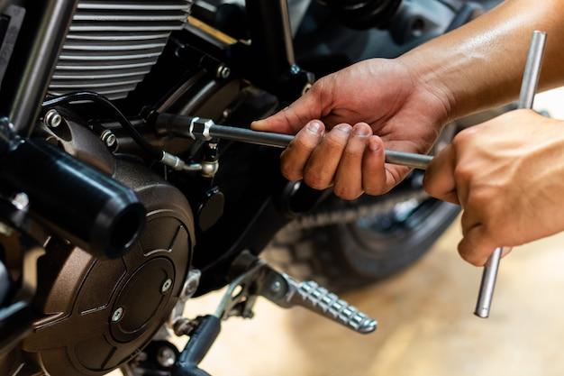 A imagem é em close up, as pessoas estão consertando uma motocicleta use uma chave inglesa e uma chave de fenda para trabalhar. Foto Premium