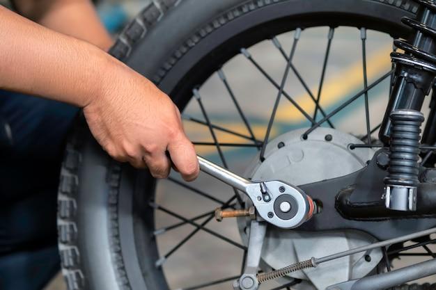 A imagem está aproximada, as pessoas estão consertando uma motocicleta use uma chave inglesa e uma chave de fenda para trabalhar. Foto Premium