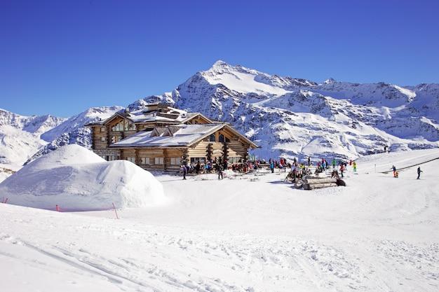 A inclinação em declive e os apres esquiam a cabana da montanha com o terraço do restaurante nos cumes italianos, europa, itália. área de esqui santa caterina valfurva Foto Premium
