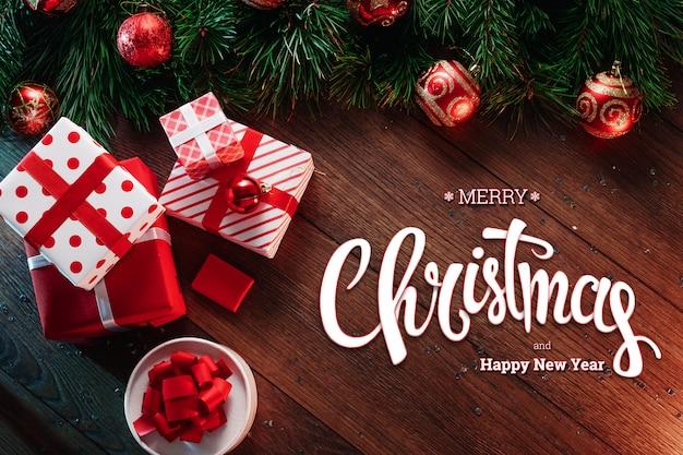 A inscrição de feliz natal, ramos de abeto verde, helicópteros e presentes em uma mesa de madeira marrom. cartão de natal, feriado. meios mistos. Foto Premium