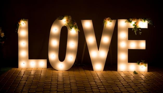 A inscrição é amor. letras grandes e brilhantes. decorações de casamento. Foto Premium