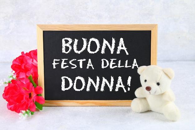A inscrição no quadro-negro em italiano: feliz dia da mulher. flores cor de rosa e ursinho de pelúcia. Foto Premium