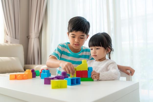 A irmã e o irmão bonitos asiáticos jogam com um designer de blocos de brinquedo em cima da mesa na sala de estar em casa. Foto Premium