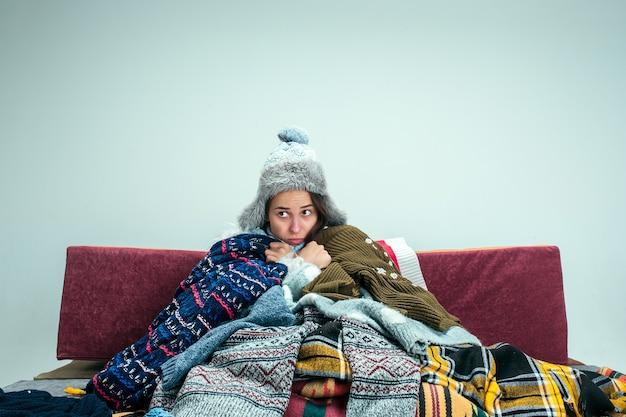 A jovem doente com gripe, sentado no sofá em casa ou no estúdio, coberto com roupas quentes de malha. doença, gripe, conceito de dor. relaxamento em casa. conceitos de saúde. Foto gratuita