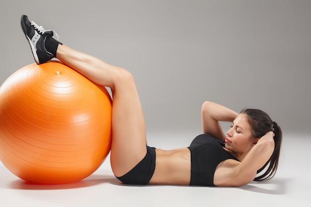 A jovem e bonita garota esportiva fazendo exercícios em um fitball Foto gratuita