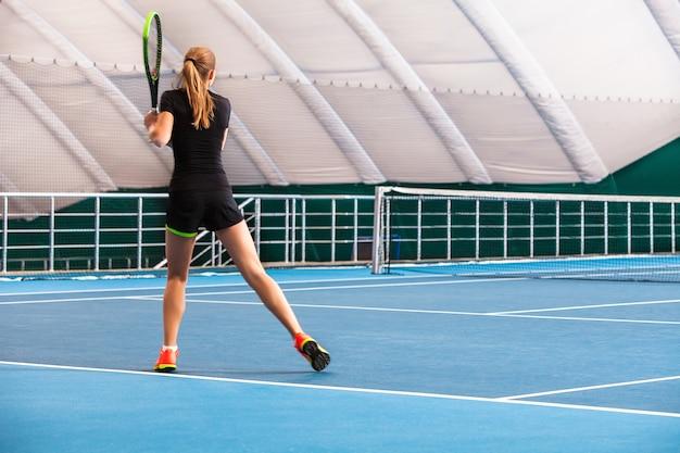 A jovem em uma quadra de tênis fechada com bola e raquete Foto gratuita