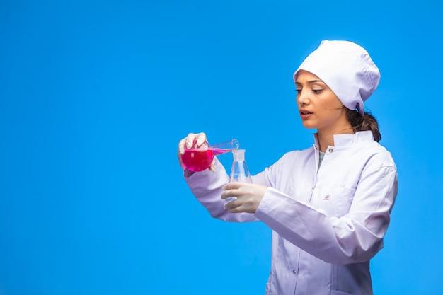 A jovem enfermeira de uniforme branco faz o teste de vírus com muita atenção. Foto gratuita