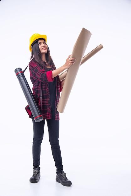 A jovem engenheira com capacete de segurança amarelo, abrindo a planta na mão, para verificar Foto Premium