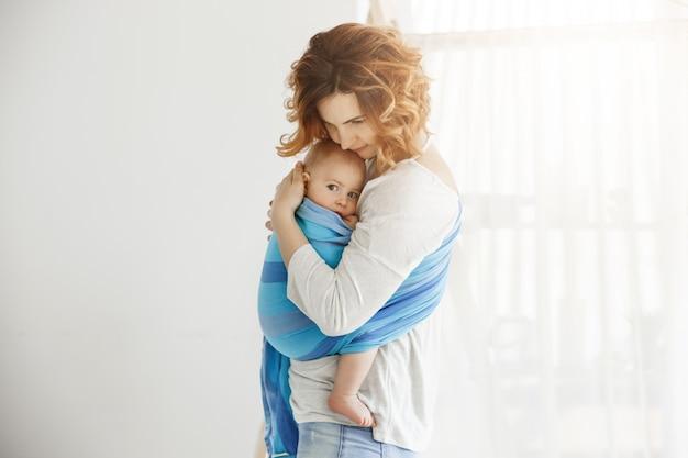A jovem mãe bonita se aconchega e acalma o filho recém-nascido, que se sente assustado após um longo sono interrompido por sons altos da rua. cena de proteção e amor. Foto gratuita