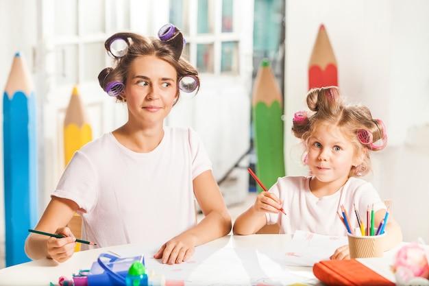 A jovem mãe e a filha pequena desenhando a lápis em casa Foto gratuita