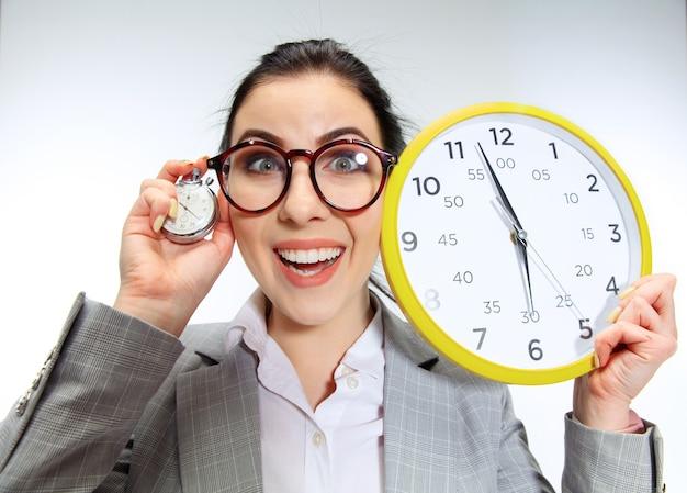 A jovem mal pode esperar para voltar para casa do escritório desagradável. segurando o relógio e esperando cinco minutos antes do fim. conceito de problemas do trabalhador de escritório, negócios ou problemas com saúde mental. Foto gratuita
