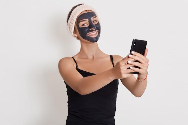 A jovem mulher aplica a máscara facial cosmética preta e guardar o telefone nas mãos isoladas sobre a parede branca. máscara de peeling facial, tratamento de beleza spa, cuidados com a pele, cosmetologia. Foto Premium