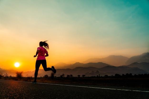 A jovem mulher aprecia correr fora com noite bonita do verão no campo. Foto Premium