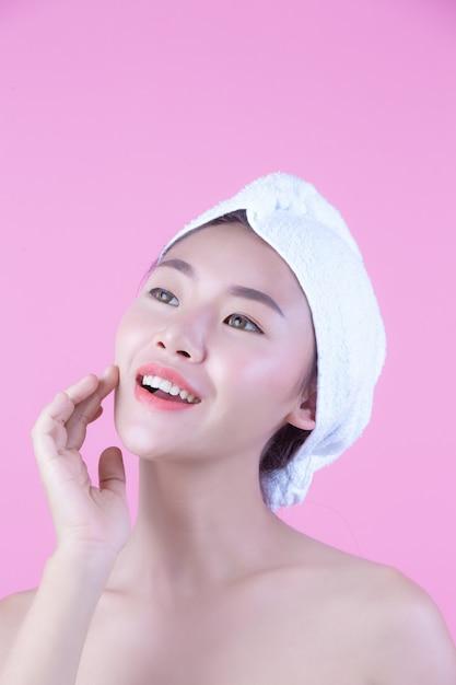 A jovem mulher ásia com pele fresca limpa toca em possuir a cara, expressões faciais expressivos, cosmetologia e termas. Foto gratuita