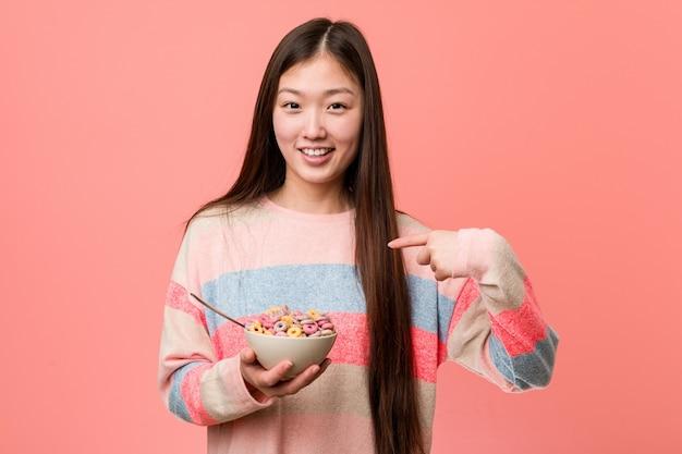 A jovem mulher asiática com uma tigela de cereal surpreendeu apontando para si mesmo, sorrindo amplamente. Foto Premium