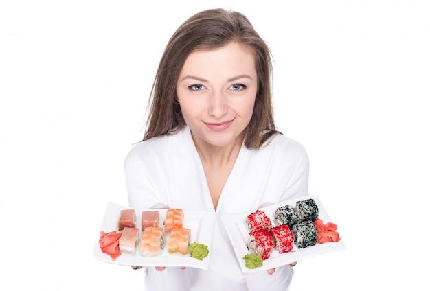 A jovem mulher bonita está guardando uma placa com sushi. Foto Premium