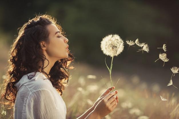 A jovem mulher bonita funde o dente-de-leão em um campo de trigo no por do sol do verão. conceito de beleza verão Foto Premium