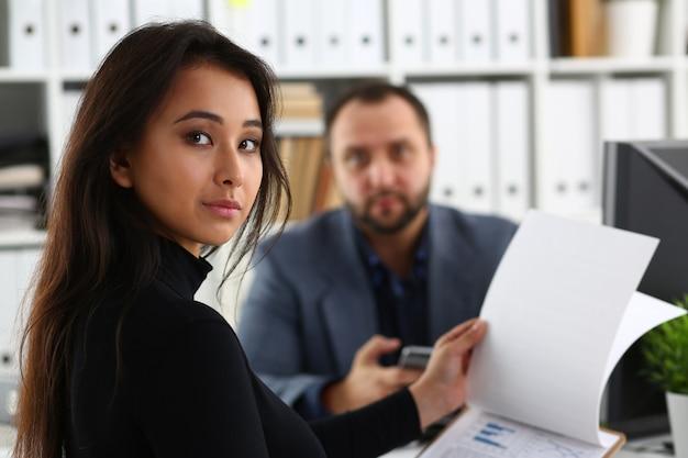 A jovem mulher bonita senta-se na cadeira na mesa no escritório no gabinete de seu chefe segurar a pasta nos braços Foto Premium