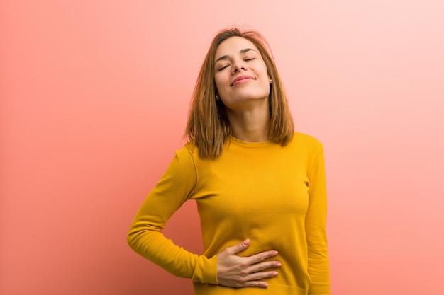 A jovem mulher consideravelmente nova toca na barriga, sorri delicadamente, comendo e conceito da satisfação. Foto Premium
