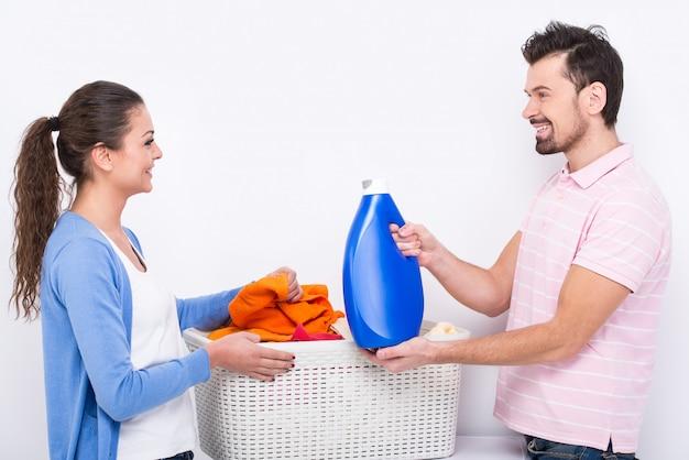 A jovem mulher e o homem estão fazendo a lavanderia em casa. Foto Premium