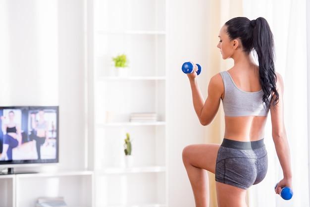A jovem mulher está exercitando com pesos em casa. Foto Premium