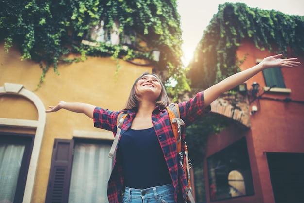 A jovem mulher feliz aprecia o curso que levanta suas mãos em urbano. conceito de estilo de vida de mulher. Foto gratuita