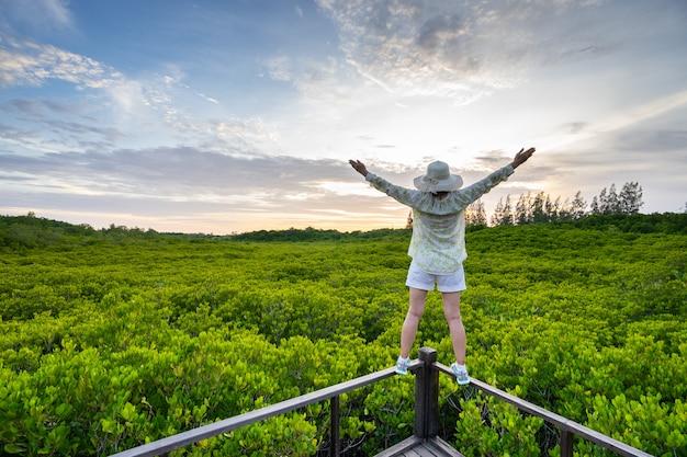 A jovem mulher feliz com mãos levanta-se na paisagem bonita da floresta dos manguezais com céu bonito. Foto Premium