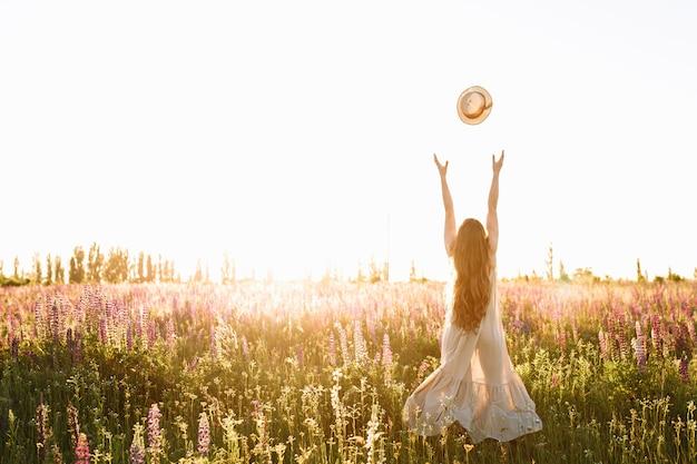 A jovem mulher joga acima o chapéu de palha no campo de flor no por do sol. Foto gratuita