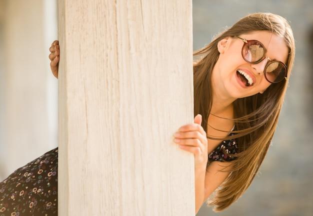 A jovem mulher nos óculos de sol está olhando a câmera. Foto Premium
