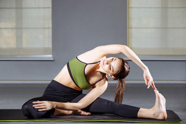 A jovem mulher que faz o esticão exercita no estúdio. ioga Foto Premium